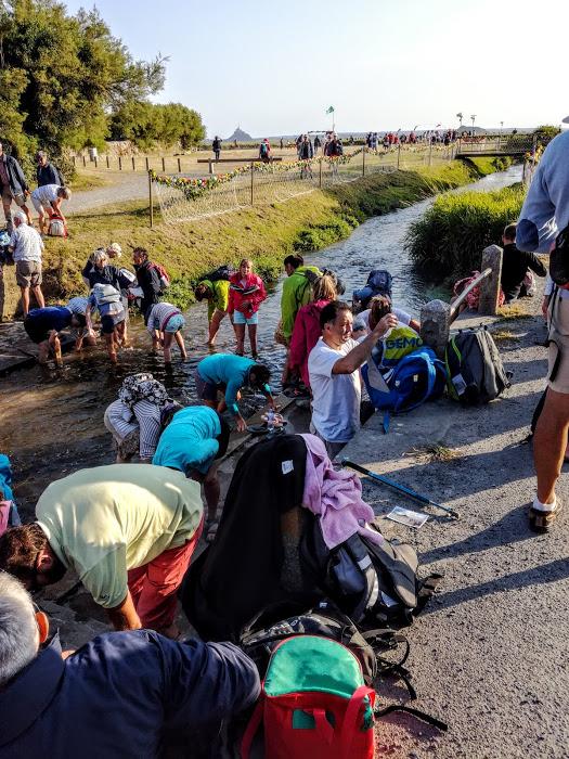 Fin du pèlerinage des grèves près du pont de Genêts. Chacun plonge ses pierre dans le Lerre pour se laver les pieds de la vase et du sable de la baie du Mont-Saint-Michel (Photo FC)