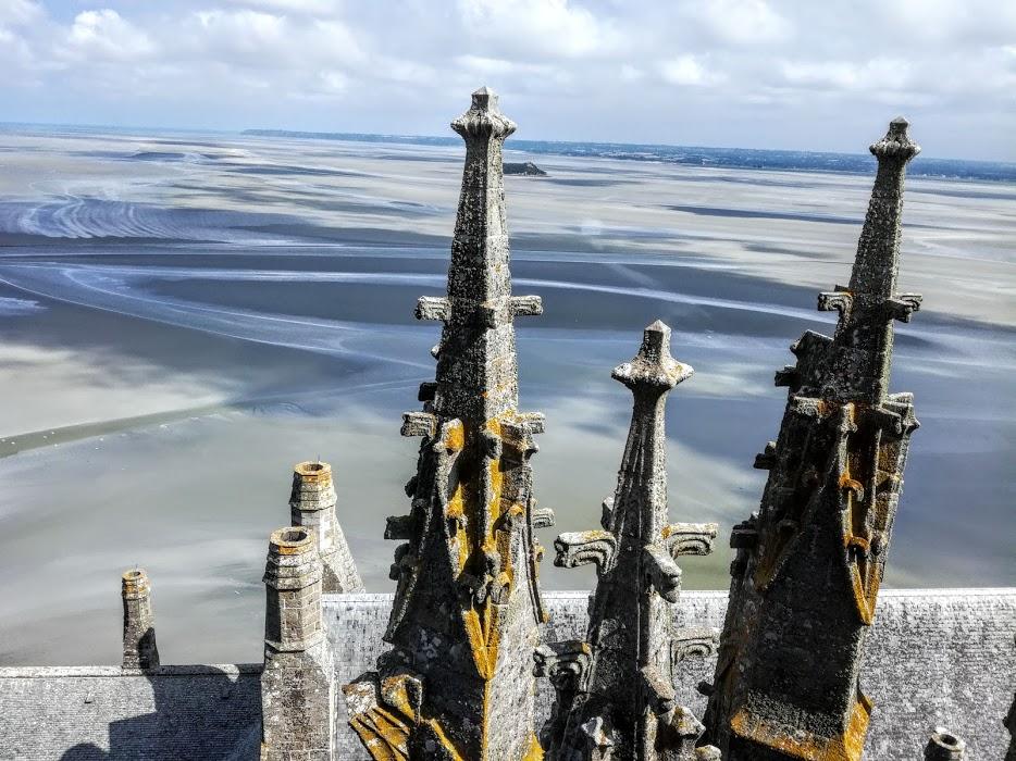 Mont-Saint-Michel, entre 2 pinacles au sommet de l'abbaye, on aperçoit l'îlot de Tombelaine qui se dresse au milieu des grèves à 2,3 km au nord. Lorsque le temps est clair, on distingue les îles Chausey d'où provient le granite qui servit à la construction de l'abbaye (Photo FC)