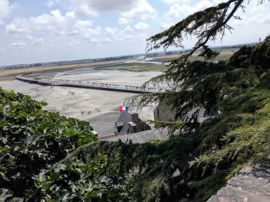 Mont-Saint-Michel. On voit le Couesnon, l'un des 3 fleuves de la baie. Il a été canalisé et régulé par un barrage. L'ancienne digue d'accès au Mont a été abattue remplacée aujourd'hui par une passerelle au-dessous de laquelle la mer a libre accès (Photo FC)