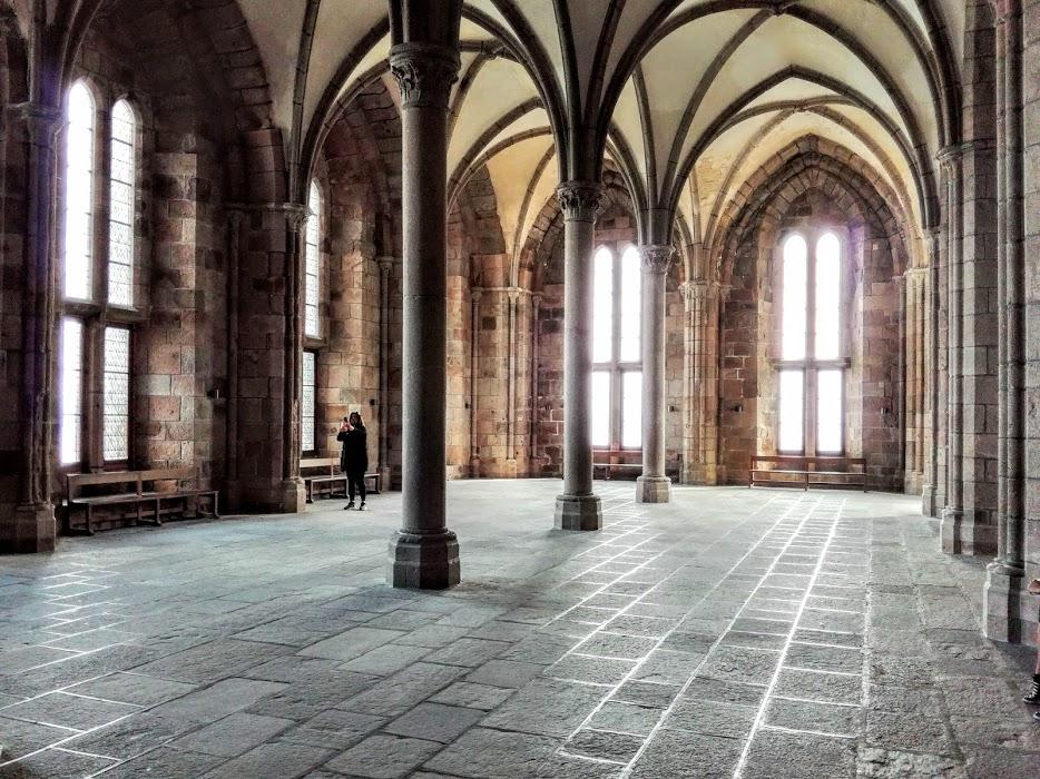 Abbaye du Mont-Saint-Michel : la salle des Hôtes. Elle est adjacente à la salle des Chevaliers et se caractérise par des colonnes très fines et des fenêtre très hautes. Le mur ouest est entièrement occupé par deux immenses cheminées. C'est sans doute là qui furent accueillis les rois qui y vinrent, de Saint Louis (Louis IX) à Charles IX (Photo FC)