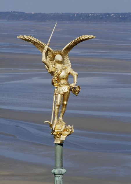 L'archange saint Michel, statue dorée perchée à 156 m de haut, au sommet de la flèche de l'abbatiale (construite par le charpentier Crepaux) a été réalisée en 1894. Elle représente Saint Michel terrassant avec une épée un dragon incarnant le mal. Elle est l'oeuvre d'Emmanuel Frémiet qui a travaillé avec Viollet le- Duc au château de Pierrefonds. Il sera payé 8 000 francs pour cela. Ses dimensions : 617 x 260 x 120 cm (socle compris). Avec les ailes, l'archange, elle mesure 4,5 m de haut pour un poids de 410 kg. En 2016, ayant fortement souffert de la foudre et des intempéries, elle sera déposée et restaurée. Elle avait été endommagée par des impacts de foudre, notamment au niveau de la pointe de l'épée qui sert de parafoudre. Elle a été restaurée avec notamment la mise en place de compléments en cuivre.