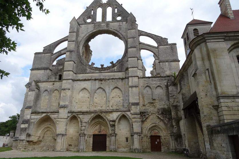 Façade principale de l'abbatiale cistercienne de Longpont, épaulée par de puissants contreforts. A droite l'entrée et le clocher de l'église paroissiale qui occupe modestement quatre travée dans la partie de l'ancien cellier.