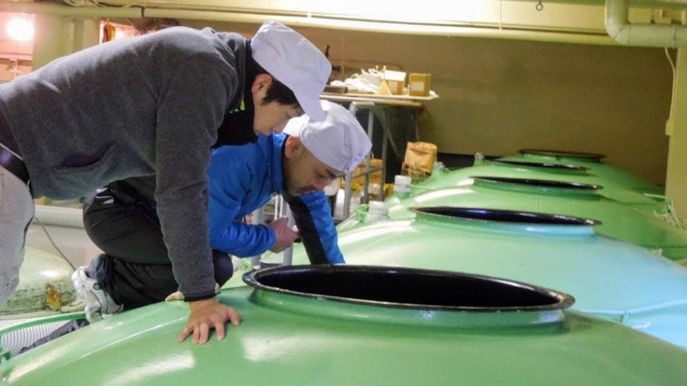 Cuves de fermentation du moût (moromi) chez Kikunotsukasa Shuzo à Morioka (Iwate). Ici les ouvriers contrôlent le taux d'alcool, de sucre et d'acidité du moût en régulant s'il le faut la température par ajout d'eau ; une température qu'il faut tenir à moins de 28° afin que l'action des levures soit complète, et qu'on obtienne un saké raffiné qui aura développé au maximum toute la richesse de ses arômes en fin de fermentation.