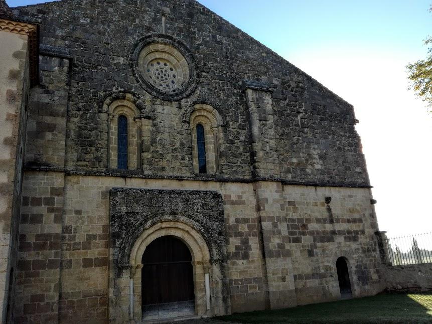 """Façade romane de l'abbatiale de Flaran. Cette façade occidentale (XII° - XIII° siècles) est soulignée par deux contreforts. Le porche, sans tympan, qui repose sur les colonnes de piédroits, s'ouvre par une triple voussure. Deux ouvertures en plein cintre, surmontées d'une rose (""""oculus""""), laissent pénétrer la lumière du couchant, dans la nef. Bâtie en pierre de taille vers 1180, l'église Notre Dame de Flaran est remarquable par ses proportions, par la rigueur de son plan cistercien et par son état de conservation, malgré des dimensions modestes (40 m de long par 19 m de large). Elle demeure caractéristique de l'art roman méridional de la deuxième moitié du XII° siècle (Photo FC)"""