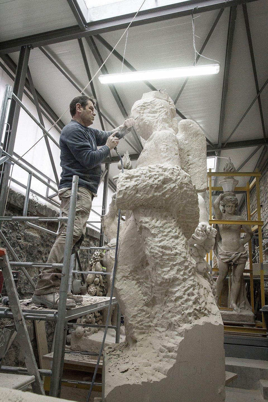 Taille directe de l'un des sculpteurs de l'une des 4 entreprises à partir d'un bloc de pierre de Saint Leu (4 tonnes et d'une hauteur de 3,50 m) Photo DR