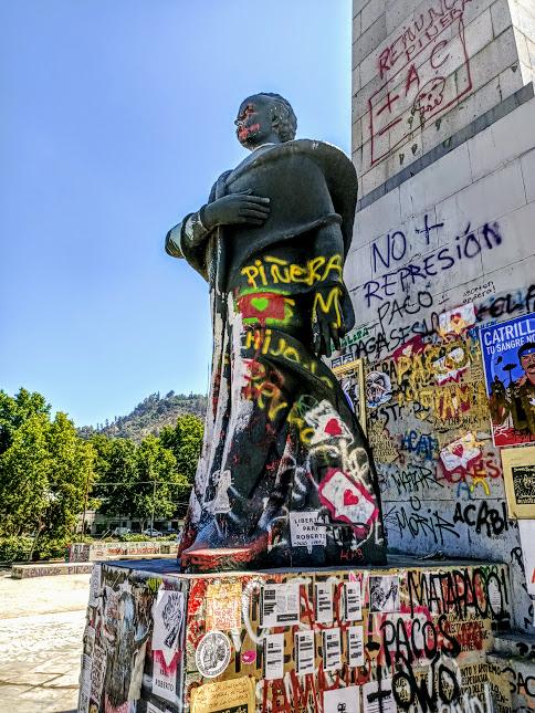 Plaza Italia, Obelisco fhanqué de la statue du président Balmaceda qui a eu droit à la vindicte des manifestants. Au loin, on aperçoit le Cerro San Cristobal qui domine la ville de ses 880 m (Photo FC)